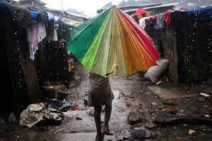 A child carries an umbrella in pouring rain in the slum of Susan's Bay in Sierra Leone's capital Freetown