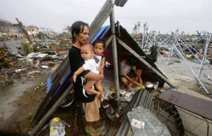 TYPHOON HAIYAN -  father by tent in ruins
