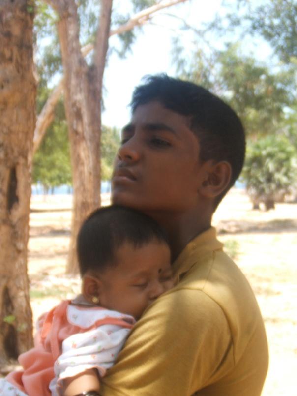 Aginas 16 cradles his sleeping 2 month old niece Safa